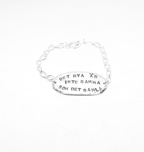 ovalt silverarmband med text med vit bakgrund