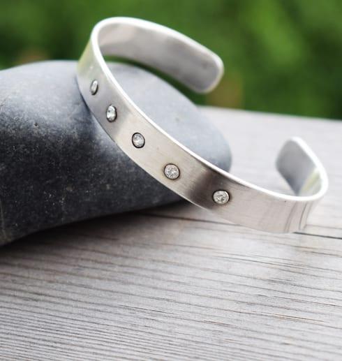 silverarmband med stenar på trä och sten