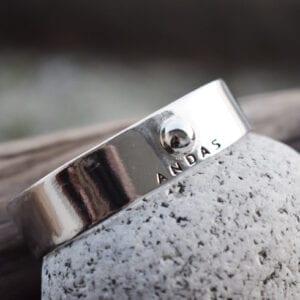silverarmband med texten ANDAS på sten utomhus