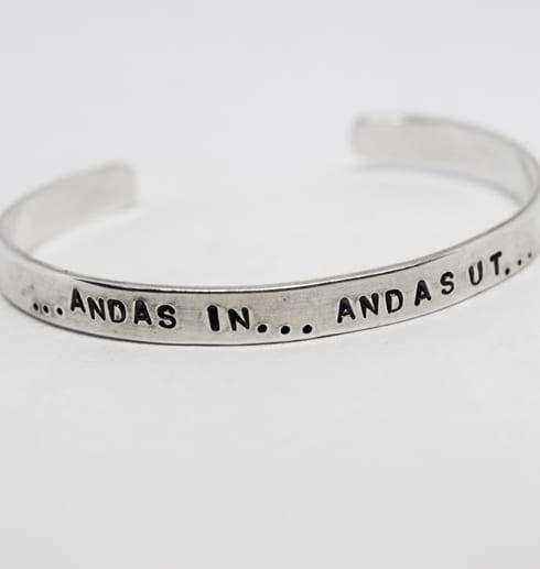 silverarmband med texten andas in andas ut på vit bakgrund