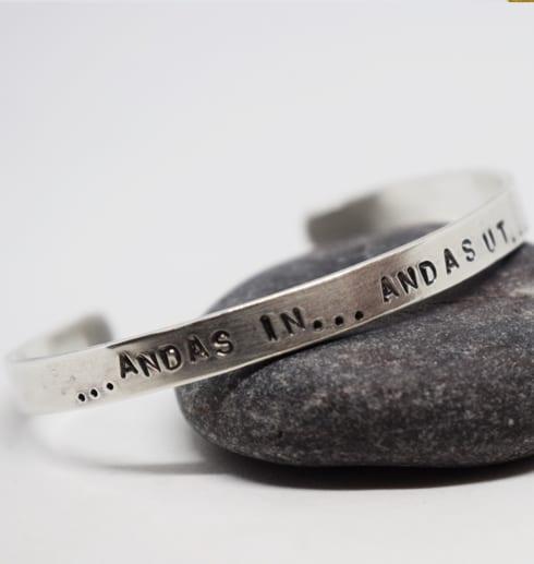 silverarmband med texten andas in andas ut på grå sten