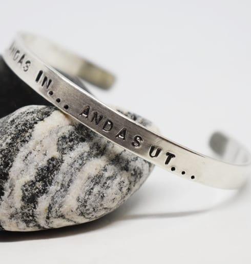 armband i silver med texten andas in andas ut på gråvit sten