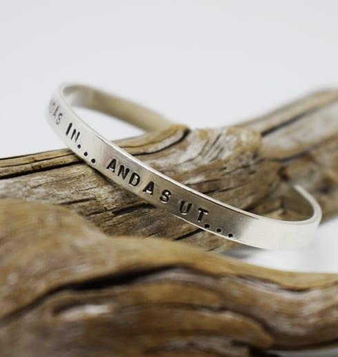 silverarmband med texten andas in andas ut på trädgren