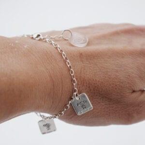 silverarmband med brickor på handled utomhus