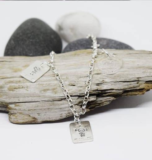 silverarmband med brickor på träbit och stenar