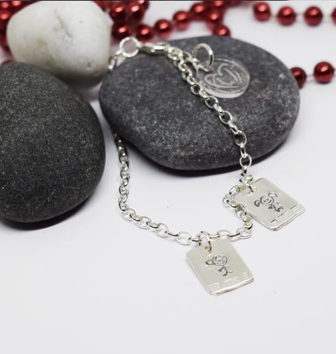 silverarmband med brickor på stenar med röda kulor bredvid