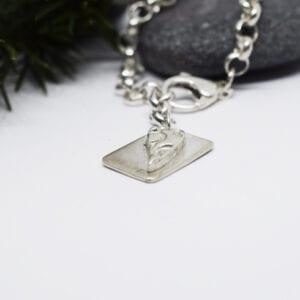 silverarmband med bricka på grå sten bakom
