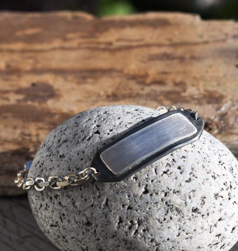 Silverarmband på sten med trä i bkagrunden