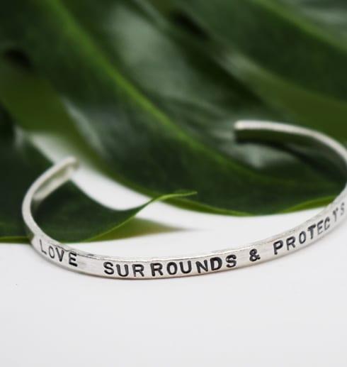 silverarmband med text litat mot ett grönt blad