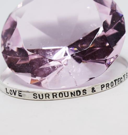 silverarmband med text med en rosa stor diamant