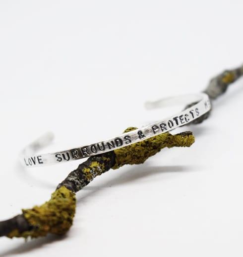 silverarmband med text på trädgren