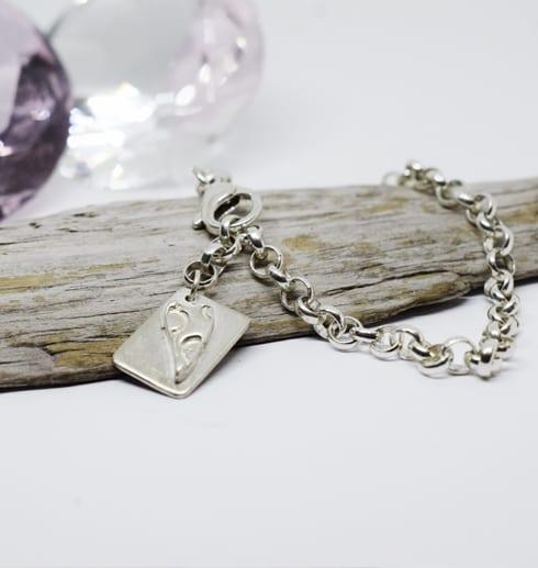 silverarmband med bricka på träbit med diamant bakom