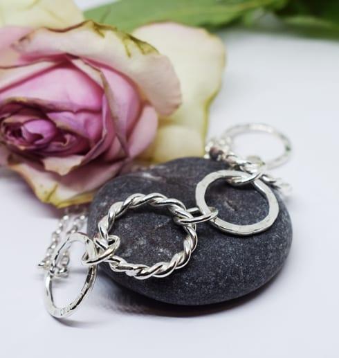 silverarmband på mörkgrå sten med gulrosa ros i bakgrunden