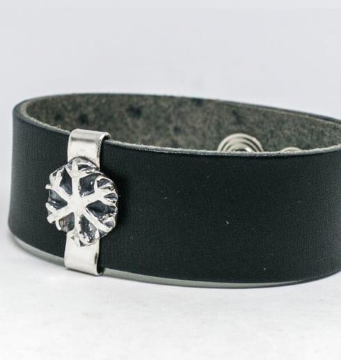 läderarmband med silversnöflingapå vit bakgrund