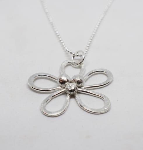 silverhalsband i form av en blomma på vit bakgrund