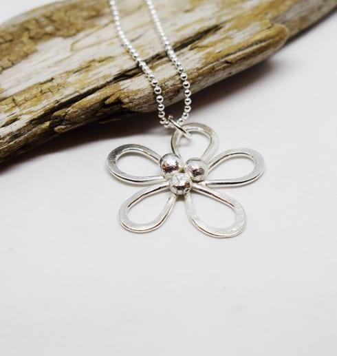 silverhalsband i form av en blomma med trädbit i bakgrunden och vit botten