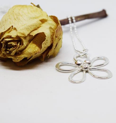 Blomma i silver mot vit bakgrund och gul blomma