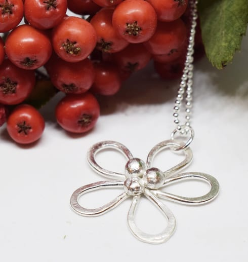 blomma i silver mot vit botten med rönnbär i bakgrunden