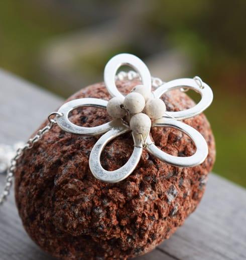 blomma i silver med vitastenar i mitten liggande på en röd sten