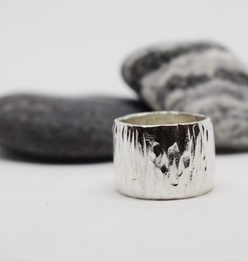 bred silverring med stenar i bakgrunden och vit botten