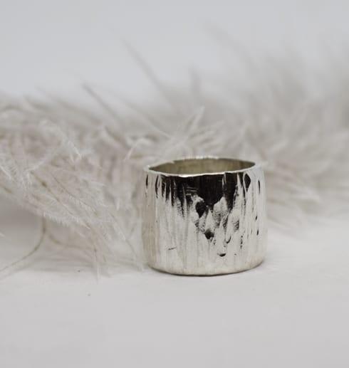 hamrad silverring med fjäder bakom