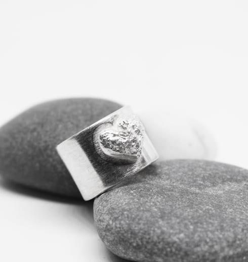 bred silverring med hjärta på grå och vitastenar