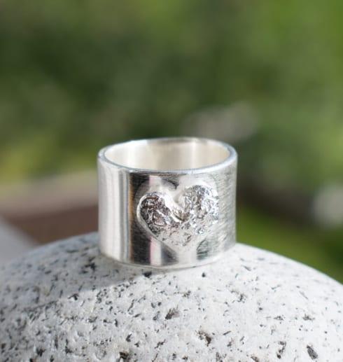 bred silverring med hjärta på sten utomhus