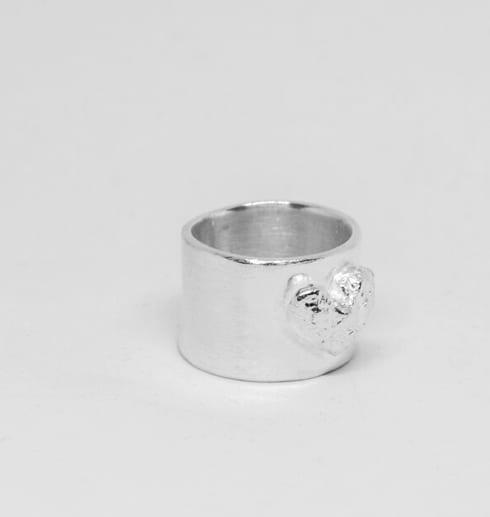 bred silverring med hjärta på vit botten