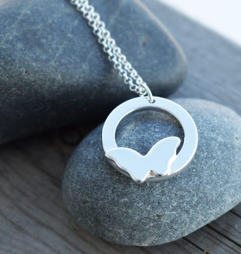 silversmycke med fjäril i kedja på stenar utomhus
