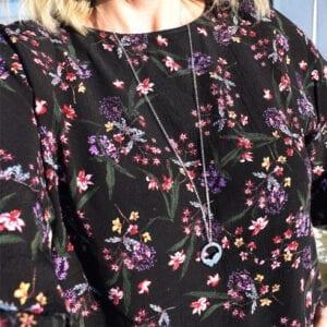 silverhalsband på kvinna med blommig blus utomhus
