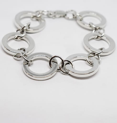 silverarmband bestående av grova ringar på vit botten