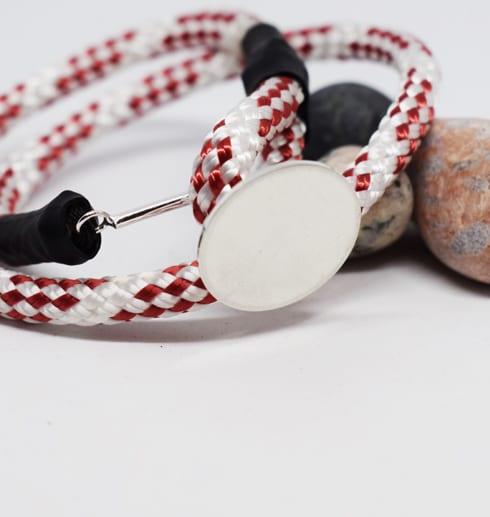 rödvitt armband med silverplatta på stenar