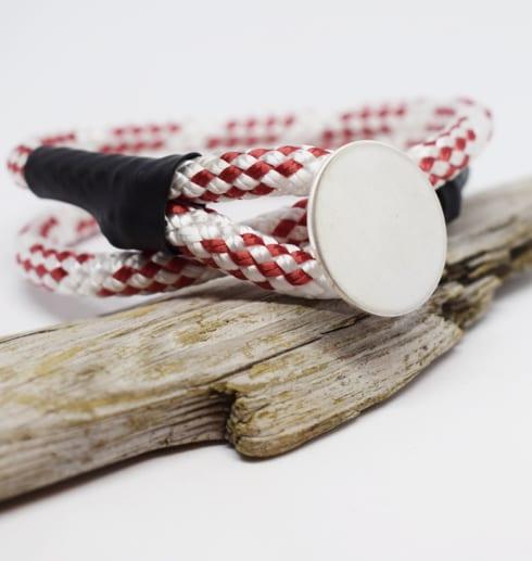 rödvitt armband med silverbricka på träbit