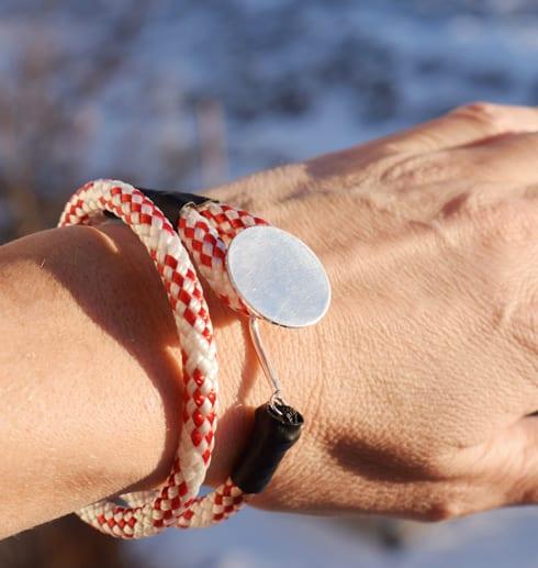 rödvitt armband med silverbricka runt handled utomhus