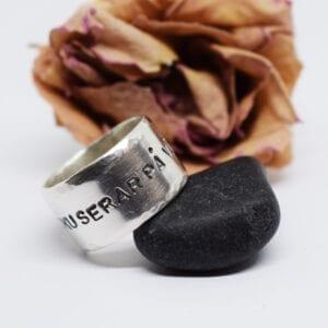 bred ring med text på svart sten med aprikos ros