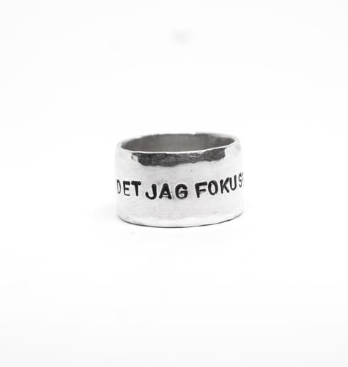 bred ring med text på vit botten
