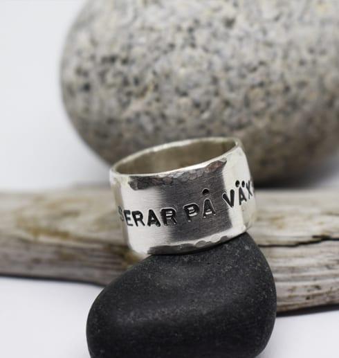 bred ring med text på svart sten med grå sten och träbit bakom