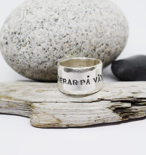 ring med text på träbit med stenar