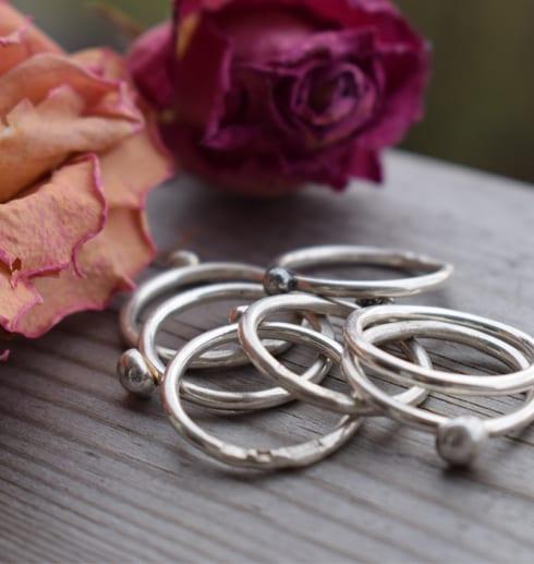 många smala silverringar på trä med rosa och aprikos ros bakom utomhus