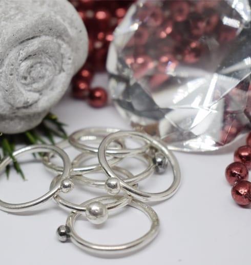många smala silverringar på vit botten med diamant, betongros och röda pärlor bakom
