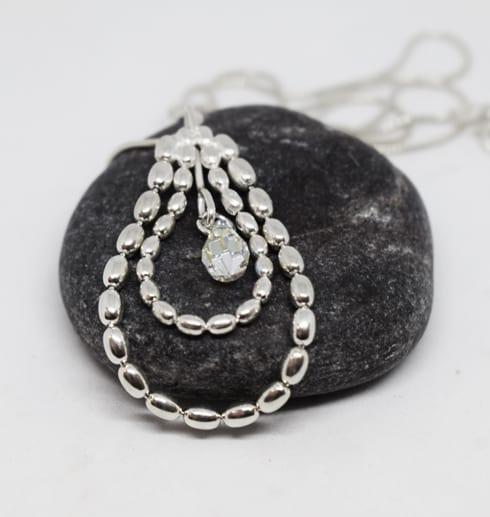 silverhalsband i kultråd på grå sten