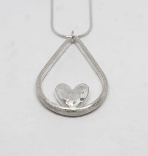 droppformat silverhalsband med hjärta i mitten på vit bakgrund