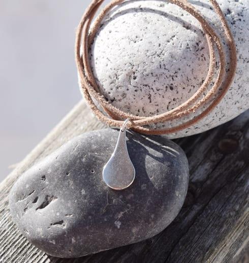 silverdroppe i brunt läderband på stenar utomhus
