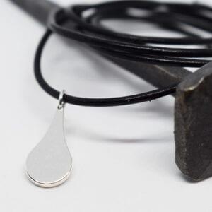 Silverdroppe i svart läderband på järnspik