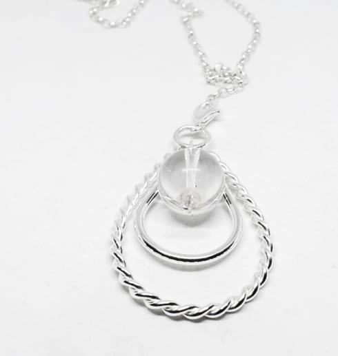silverhalsband i form av en droppe på vit botten