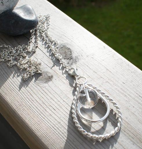 silverhalsband i forma av en droppe på trä utomhus