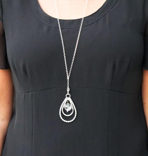silverhalsband i form av en droppe på kvinna med svart klänning