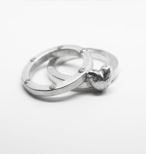 två silverringar med hjärta och stenar på vit bakgrund