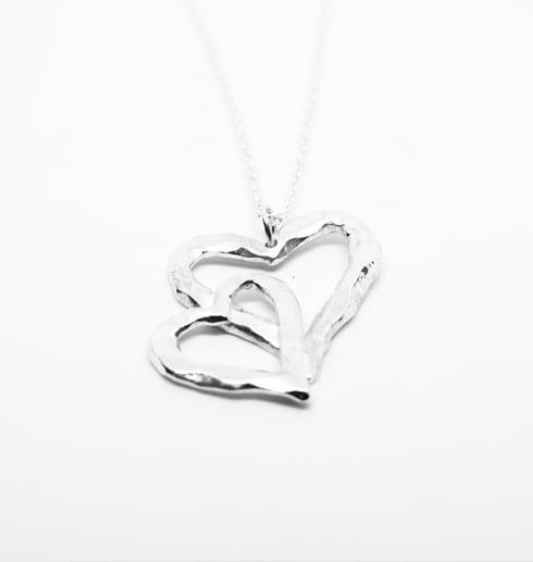 silverhalsband i form av ett dubbelhjärta på vit bakgrund