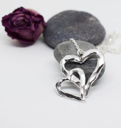silverhalsband i forma av ett dubbelhjärta på stena med ros bakom